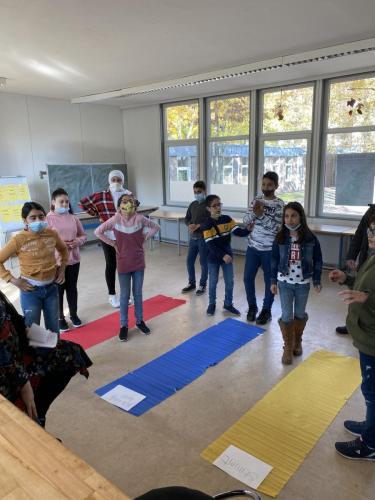 Drei Streifen auf dem Boden repräsentieren verschiedene Antworten. Die Kinder aus der Gruppe stehen je nach Antwort auf einem der Streifen.