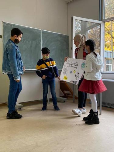 Die Kinder präsentieren ein gebasteltes Plakat zu Kinderrechten.