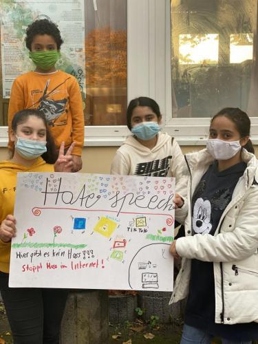 Kinder Präsentieren ein Plakat zu Hatespeech.