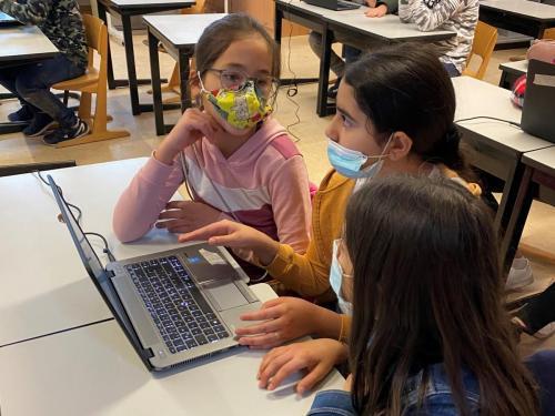 Drei Mädchen recherchieren an einem Laptop.